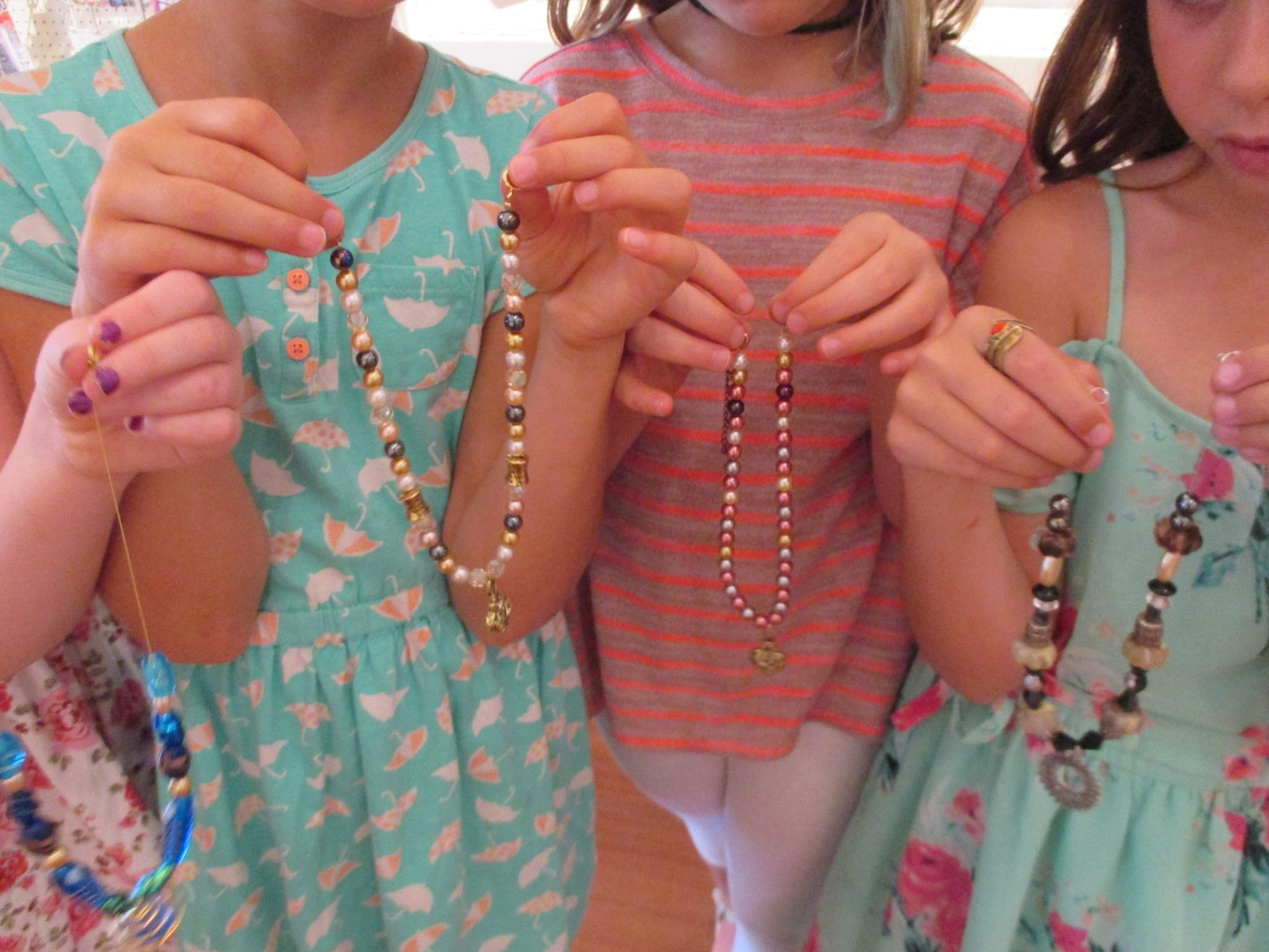girls holding beaded jewellery